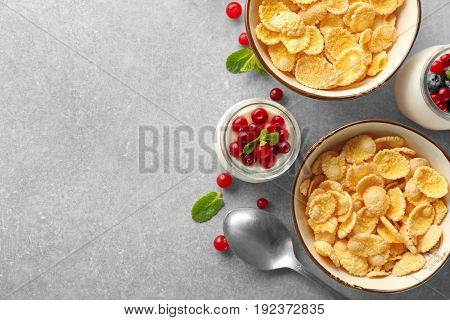 Tasty breakfast with corn flakes on light background