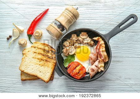 Frying pan with tasty egg, bacon and mushrooms on table