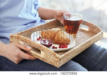 Wicker tray with delicious breakfast on human's knees