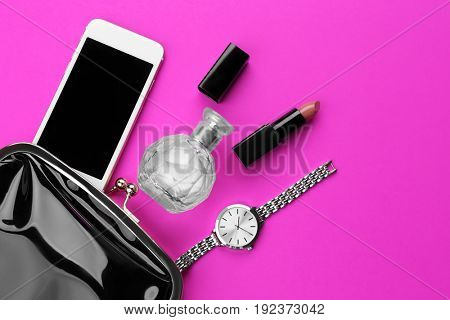 Perfume bottle with cosmetic bag and phone on color background
