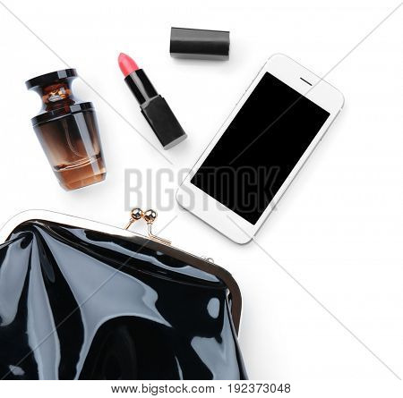 Perfume bottle with cosmetic bag and phone on white background