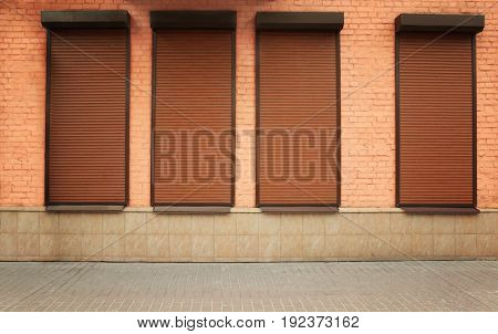 Windows with closed roller blinds in wall