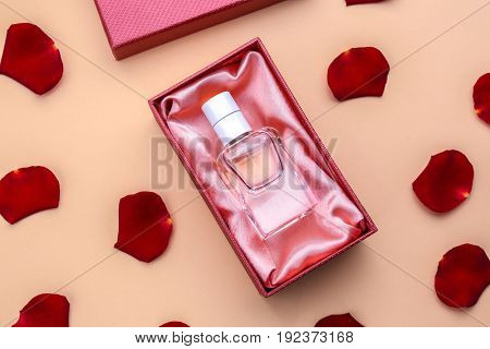 Perfume in present box on color background