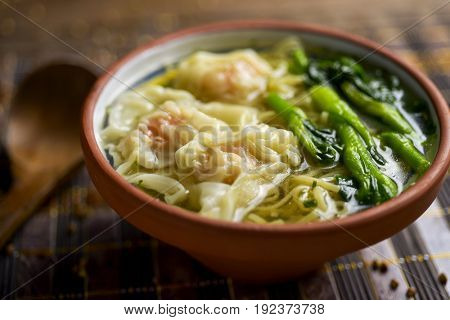 closeup of an earthenware bowl with shrimp wonton noodle soup with choy sum, placed on a table set for lunch or dinner