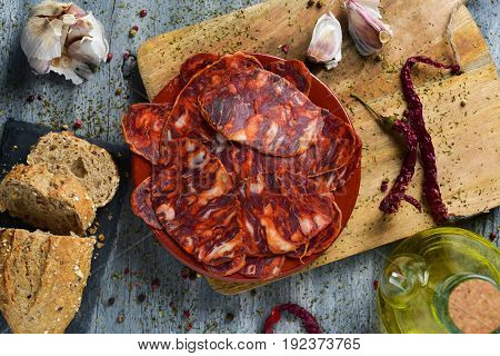 high-angle shot of an earthenware plate with some slices of spanish chorizo, cured pork sausage, some slices of bread, a glass cruet with olive oil and some garlics, on a rustic gray wooden table