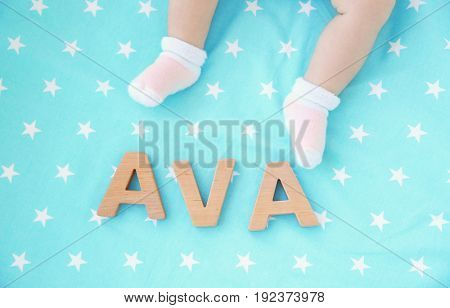Legs of cute baby and word AVA composed of wooden letters on bed. Choosing name concept