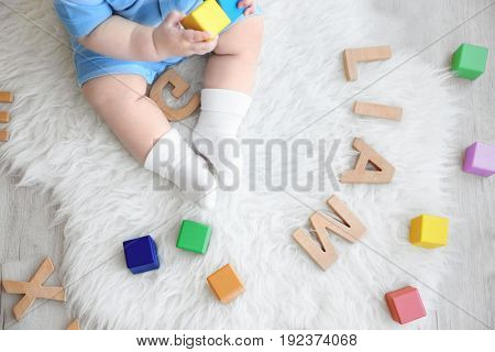 Cute baby sitting on floor with word LIAM composed of wooden letters. Choosing name concept