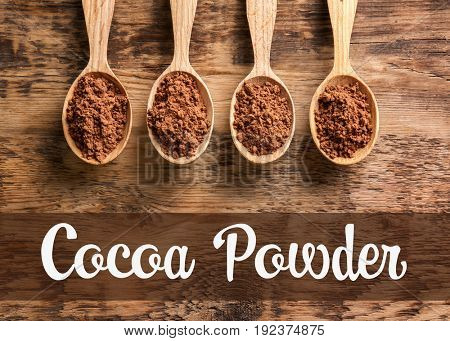 Spoons and cocoa powder on wooden background