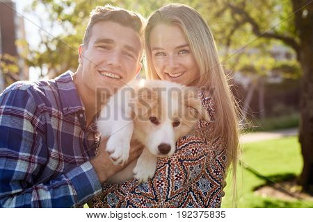 Attractive couple holding hugging their puppy in the park, smiling with sun flare behind