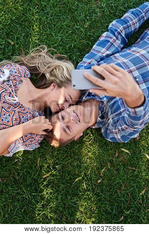 Overhead view of happy couple in love using smartphone to take loving selfie, lying down on grass