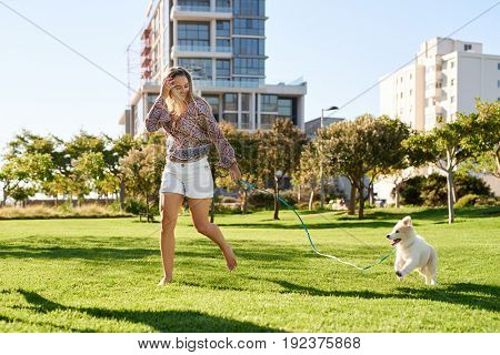 Smiling woman playing running with puppy in the park, candid moment between pet dog and owner