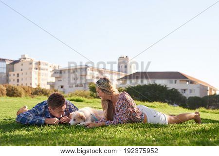 Couple lying down on grass with their cute puppy, clear sunny summer day