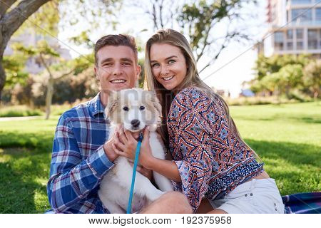 Young loving couple smiling with their adorabe adopted puppy dog in green park