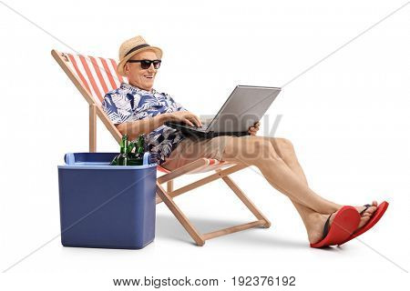 Elderly tourist with a laptop sitting in a deck chair next to a cooling box filled with bottles of beer isolated on white background
