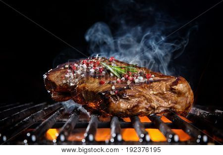 Beef steak on the grill grate, flames on background. Barbecue and grill, delicious food.