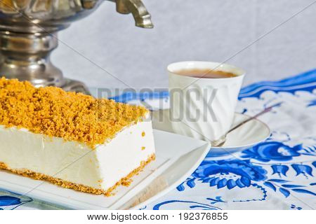 Exquisite white cheesecake, sprinkled with sweet orange crumbs. The background is samovar and porcelain white cup with hot tea on blue kitchen towel. Professional bakery