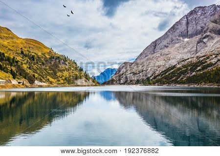 The concept of ecological and extreme tourism. The magic and harmony of the Dolomites. Glacial lake with clear cold water. Mountain Lake Lago di Fedaia, Dolomites
