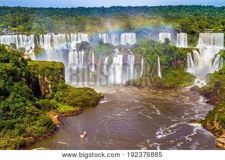 The concept of extreme and exotic tourism. Iguazu Falls National Park on the border of Argentina, Brazil and Paraguay. Small boats transport curious tourists to waterfalls