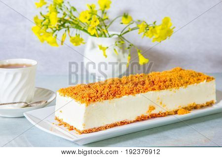 Gorgeous white cheesecake, sprinkled with sweet crumbs. Professional bakery. The background is  vase with daisies and porcelain cup with hot tea