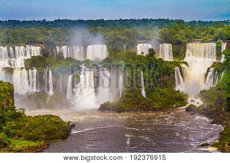 Boiling water creates a watery dust and a rainbow. Several waterfalls from Iguazu Falls. The concept of extreme and exotic tourism