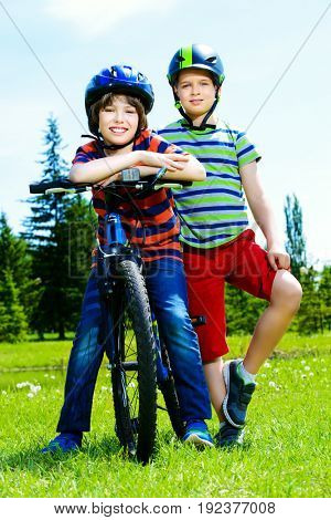 Happy boys are riding bikes in the park. Happy summer holidays.