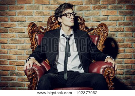 Glamorous sexy young man in elegant black suit and glasses sitting in vintage armchair. Male beauty, fashion.