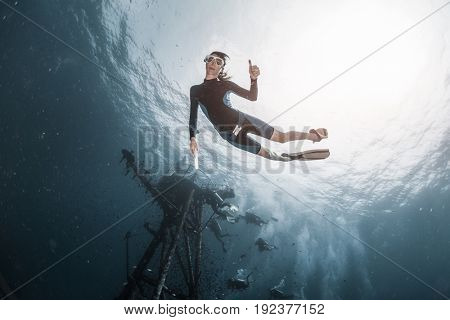 Underwater shot of woman free diver swimming near the ship wreck