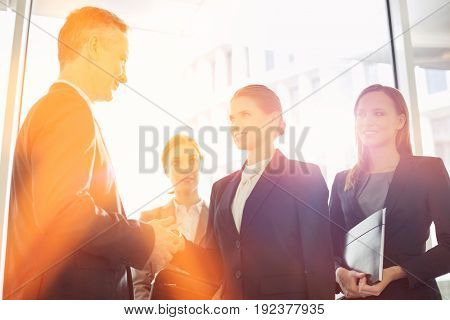 Businesswoman giving her card to businessman in office