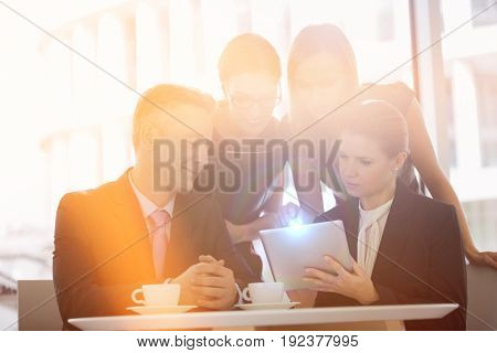 Business people using digital tablet together in office cafeteria