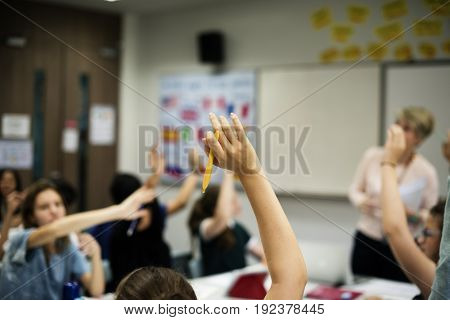Group of diverse high school students with arms raised