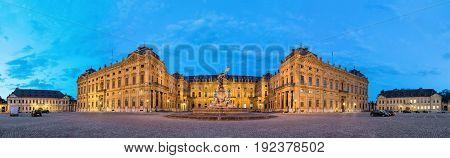 Panoramic view of illuminated Wurzburg Residence palace from Residenzplatz square in the evening Wurzburg Germany