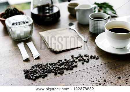 Coffee beans and a cup of coffee on a wooden table