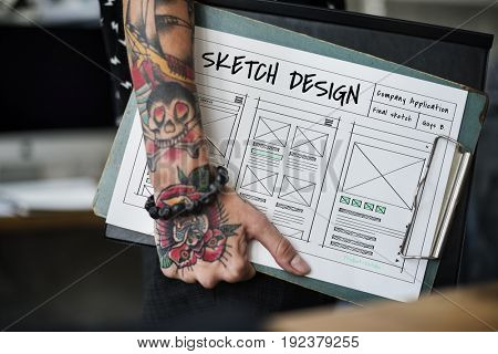 Tattoo hand hold a website design layout board