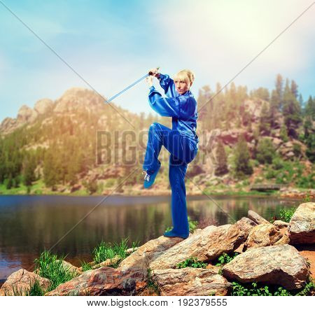 Wushu master with sword against lake and mountains