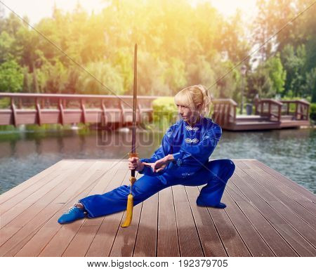 Female wushu fighter with blade against lake