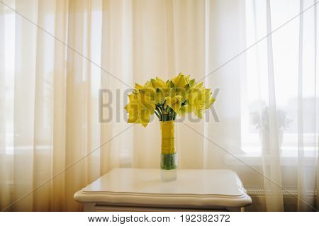 Yellow flowers in bride boquete with yellow stripe. Bouqquete standing on a white retro table in style hotel. Close up view. Broun yellow color.