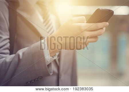 Businessman hand using smartphone at train station, with beautiful sun flare at background.