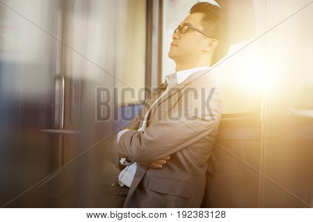 Asian businessman taking a nap inside train while travelling to work. poster