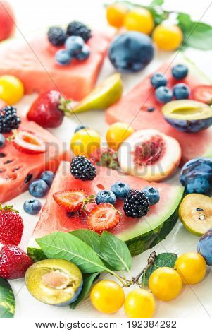 variation of summer berries and fruits cutted in pieces on white wooden background