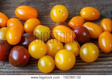 Cherry tomatoes on rustic wooden background. Raw vegetarian food.