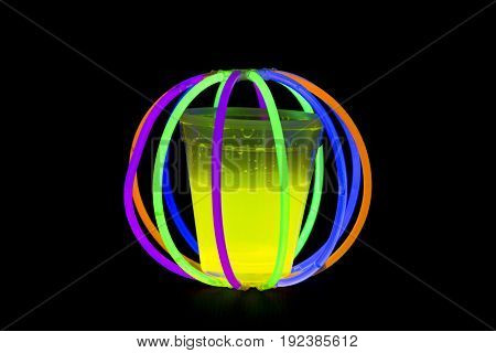 Yellow fluorescent glass in ball with glow sticks neon light on back background. variation of different colored chem lights