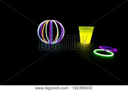 Yellow fluorescent glass and ball with glow sticks neon light on back background. variation of different colored chem lights