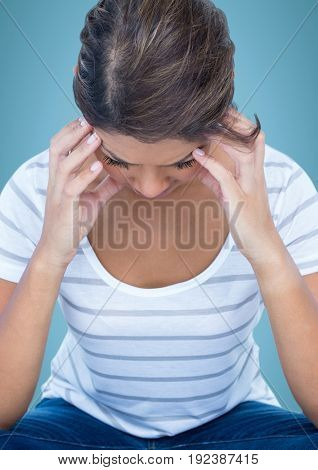 Digital composite of Woman hands on temples against blue background