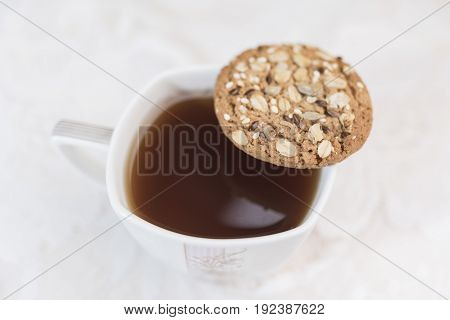 Homemade cookies with cereals and sunflower seeds lying on top of a cup of tea on a white background