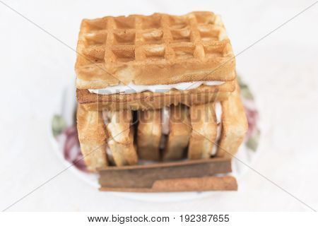Viennese waffles with cream filling and one stick of cinnamon lie on a white saucer with a floral pattern in the defocus on a white background