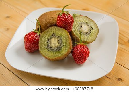 Kiwi with strawberry on plate on wood table