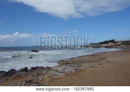 Porto beach coast, waves crash in cliffs