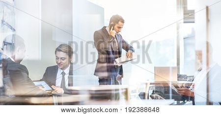 Businessman executive talking on mobile phone in modern corporate office, holding financial newspaper checking time on wriswatch. Glass reflection of business people meeting in office. Time is money.