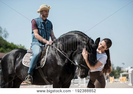 handsome man in cowboy hat sitting on horseback while woman stroking horse