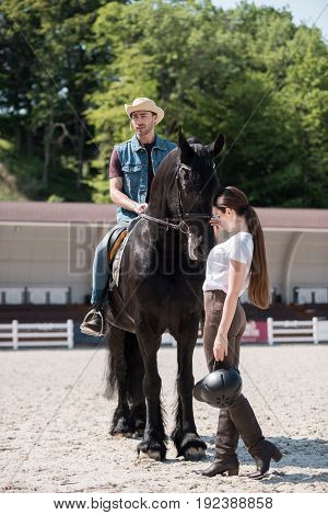 young man in cowboy hat sitting on horseback while woman stroking horse